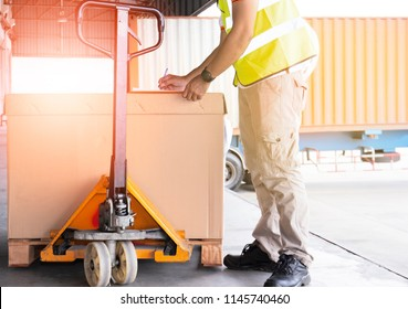 Warehouse worker writing on a clipboard checking a pallet shipment for loaded into a truck