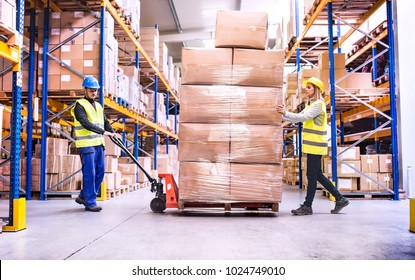 Warehouse workers pulling a pallet truck.