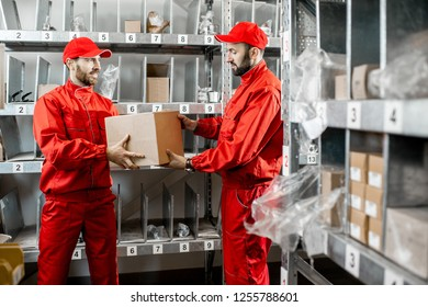Warehouse workers in red uniform during the work in the storage