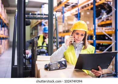 Warehouse workers with smartphone working together.