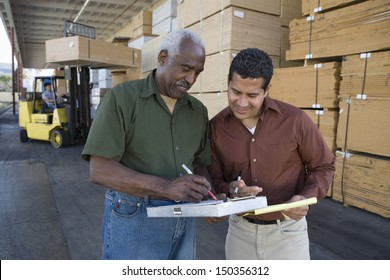 Warehouse workers stocktaking in timber factory