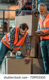 warehouse workers using digital tablet and adhesive tape while packing boxes