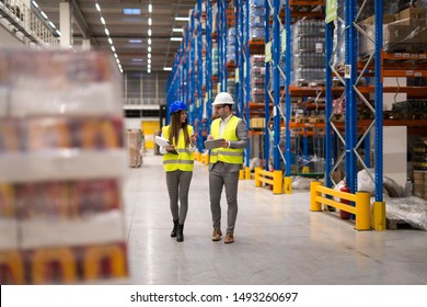 Warehouse workers walking through large storage department discussing about distribution and logistics. Warehouse interior with palette of goods and shelves.