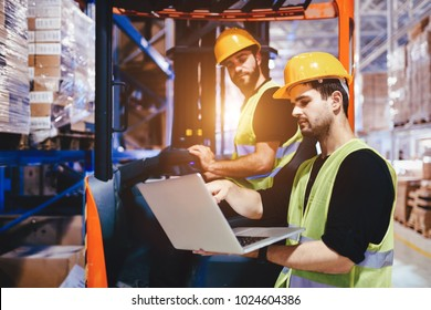 Warehouse workers working together with forklift loader