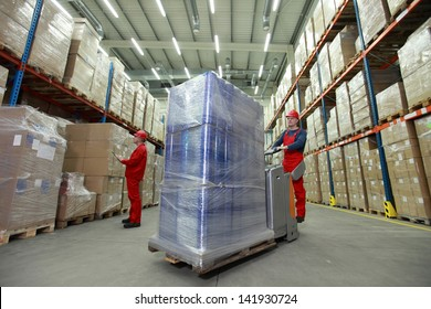 warehousing - management of the flow of resources - two workers in uniforms and safety helmets working in storehouse