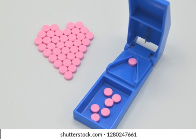 Warfarin tablets in the shape of a heart and a pill cutter. Warfarin sodium is a Vitamin K antagonist which is used for preventing blood clots. Proper dose may require the use of a pill cutter.