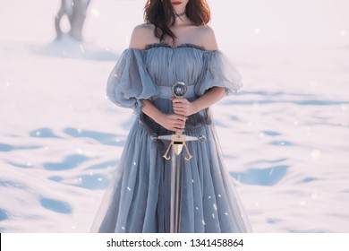 warlike girl brunette hair long blue vintage dress beautiful young lady. winter nature snow. sharp silver sword in hands goddess of death character computer game. mysterious woman silhouette red lips
