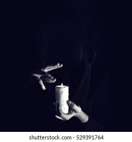 Warlock holds hands over burning candle in darkness