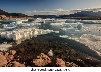 Warm afternoon light shining on icebergs while floating in harbor at Qikiqtarjuaq, Nunavut, Canada