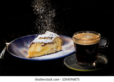 Warm apple cake with coffee - with a sprinkle of icing sugar on it