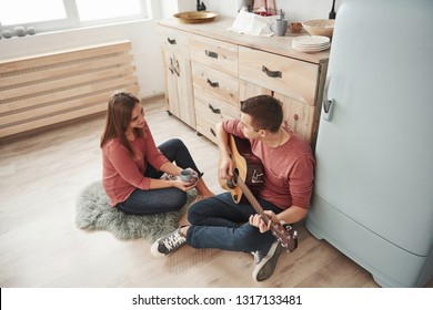 Warm atmosphere. Young guitarist playing love song for his girlfriend in the kitchen.