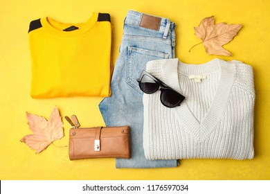 Warm autumn clothes and accessory on orange background. Top view.