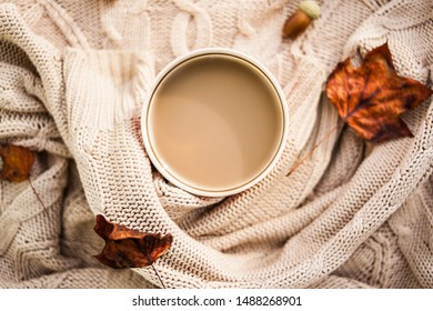 warm autumn. cup of coffee wrapped in a woolen beige sweater. still life