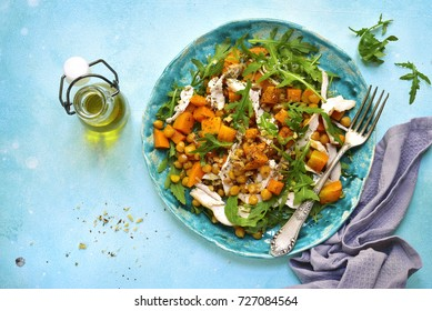 Warm autumn salad with pumpkin,chickpea,arugula and grilled chicken on a plate over light blue slate,stone or concrete background.Top view.