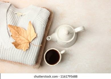 Warm autumn sweaters and tea on neutral background. Concept autumn clothes.