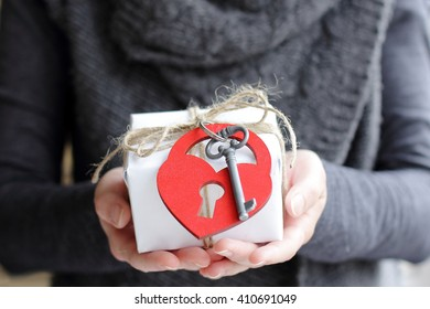 warm background with a gift and attached to it the key and heart/I wish warmth and love