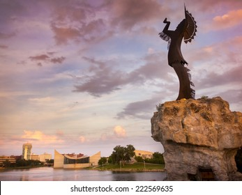 A warm, beautiful sunset along the Arkansas River in Wichita, Kansas. The Keeper of the Plains in the foreground stands more than seventy feet tall including its promontory.