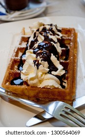 Warm Belgian waffle with whipped cream and chocolate topping served on a plate