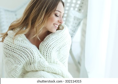 a warm blanket in the hands of a beautiful woman