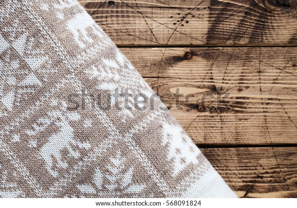 A warm blanket with a Scandinavian pattern on wood background - hygge concept