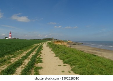 Warm blue skies over iconic red and white lighthouse in Happisburgh, North Norfolk, England, UK