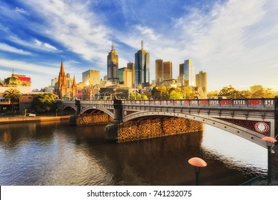 Warm bright sunlight lit Melbourne city over Princes bridge St Kilda road sun sunrise over waters of Yarra river.