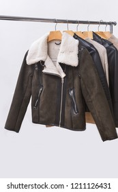 warm brown jacket with sweater ,black leather jacket clothes on hanger