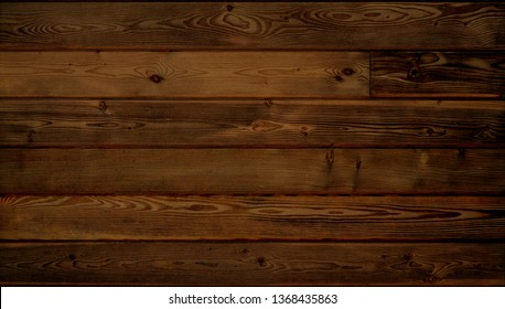 Warm brown wood surface with aged boards lined up. Wooden planks on a wall or floor with grain and texture.