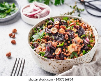 Warm buckwheat and beetroot salad on gray background. Vegetarian diet idea and recipe -salad with beetroot, buckwheat, mushrooms, onion, fresh herbs,hazelnut