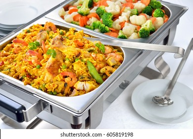 Warm buffet with Spanish paella and mixed buttered vegetables served in a chafing dish