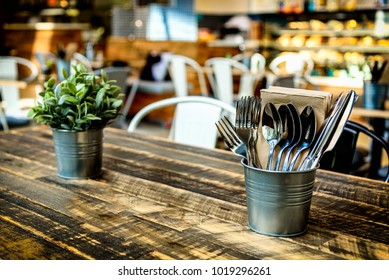 A warm cafe interior with wooden table, cutlery, pot plant and food counter in the background