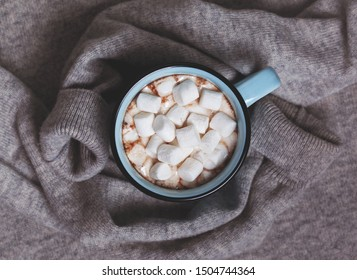 warm cashmere sweater,  a cup of hot chocolate and marshmallows . view from above.
