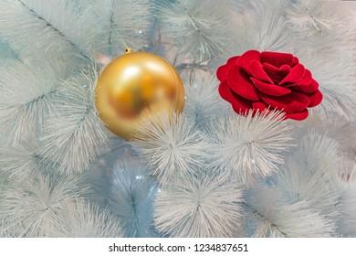 warm Christmas atmosphere close up of white Christmas tree with gold decorative ball  , atmosfera accogliente con albero di natale bianco con rosa e palla dorata