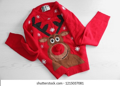 Warm Christmas sweater on white wooden background. Seasonal clothing