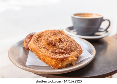 Warm cinnamon bun with icing sugar with a cup of coffee lying in a street cafe.