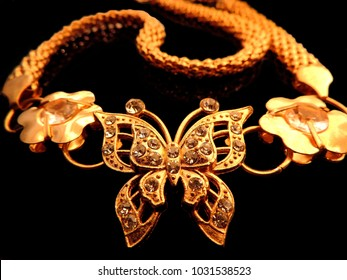 warm close up image of glittering gold jewelry of diamonds studded butterfly with gold flowers on either sides in symmetry and thick braided gold belly belt on a dark black background