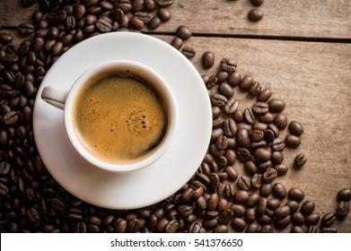 warm coffee cup and coffee beans on table