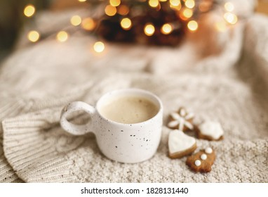 Warm coffee in stylish cup on background of cozy knitted sweater with christmas gingerbread cookies and warm lights. Atmospheric winter hygge. Happy Holidays