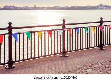 warm color sunset at the seaside with fence and colorful flags
