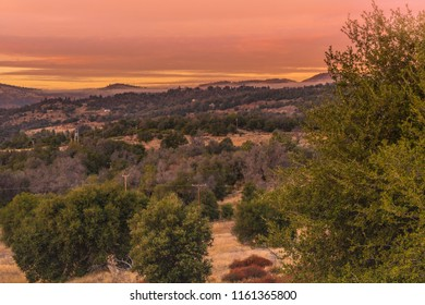 Warm color sunset sky, orange, red, lavender tones, in southern California hills in autumn, oaks in foreground mountains in background