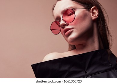 Warm colored fashion portrait of beautiful young woman in round red sunglasses and grey latex jacket posing in studio