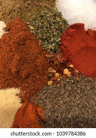Warm colored spices ready for cooking. Cumin, oregano, paprika, chili powder, salt and pepper arranged on a countertop.