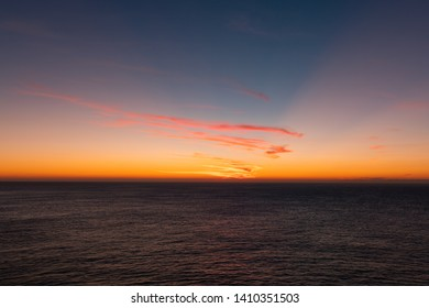 Warm colorful sunrise sky over the ocean horizon.
