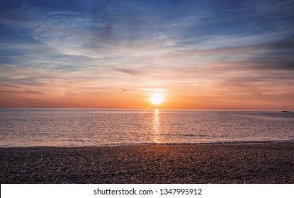 Warm colorful sunset sky over calm sea shore at low tide in Aberystwyth, North Wales