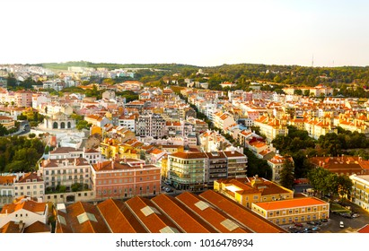 The warm colors of Alcantara neighorwood at sunset seen from the 25 de Abril Bridge new belvedere, in Lisbon, Portugal