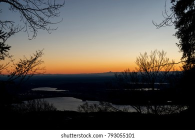 Warm colors of the sunset, landscape in winter season with alps at the horizon and lakes in foreground seen from mountain Campo dei Fiori over the Varese city