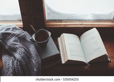 Warm and comfy winter concept. Book, cup of lemon tea and sweater on wooden window sill in old house. Reading and relaxing in cold snowy weather at home. Quiet silent homely scene.