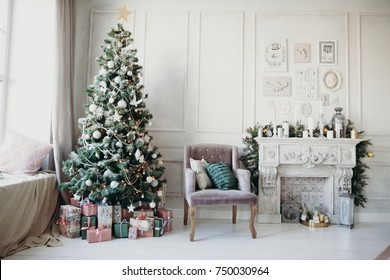 warm cozy beautiful modern design of the room in delicate light colors decorated with Christmas tree and decorative elements fireplace