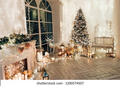 warm and cozy evening in Christmas interior design,Xmas tree decorated by lights presents gifts,toys, deer,candles, lanterns, garland lighting indoors fireplace.holiday living room.magic New year