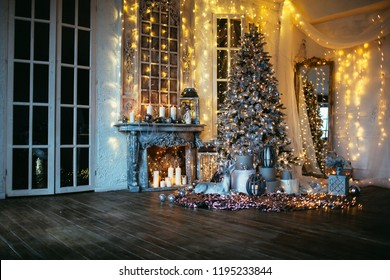 warm and cozy evening in Christmas room interior design, Xmas tree decorated by lights presents gifts toys, candles, lanterns, garland lighting indoors fireplace.holiday living room. New year holidays